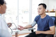 Γιατρός που μετρά τη πίεση του αίματος στοκ εικόνες