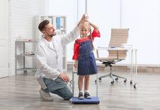 Γιατρός που μετρά το ύψος μικρών κοριτσιών ` s Στοκ Εικόνα