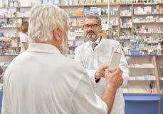 Γιατρός που μιλά με το ηλικιωμένο άτομο στο φαρμακείο στοκ εικόνες με δικαίωμα ελεύθερης χρήσης