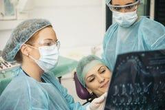 Γιατρός που μιλά με τον ασθενή της και που διδάσκει μια ακτηνογραφία Στοκ Φωτογραφίες