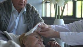 Γιατρός που μιλά σε μια άρρωστη ηλικιωμένη γυναίκα και το σύζυγό της στο σπίτι απόθεμα βίντεο