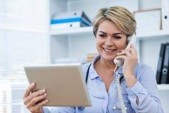 Γιατρός που μιλά στο τηλέφωνο χρησιμοποιώντας την ψηφιακή ταμπλέτα Στοκ Εικόνα