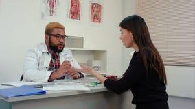 Γιατρός που ορίζει τα χάπια στο θηλυκό ασθενή και που εξηγεί τη δόση απόθεμα βίντεο
