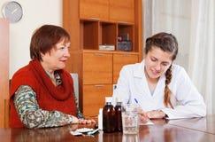 Γιατρός που ορίζει το φάρμακο στην ανώτερη γυναίκα Στοκ Φωτογραφίες