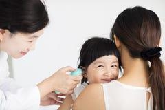 γιατρός που παίρνει τη θερμοκρασία που χρησιμοποιεί στο θερμόμετρο αυτιών Στοκ Εικόνες
