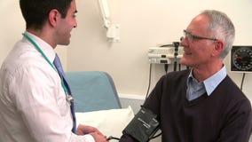 Γιατρός που παίρνει τη πίεση του αίματος του ανώτερου αρσενικού ασθενή απόθεμα βίντεο