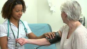 Γιατρός που παίρνει τη πίεση του αίματος του ανώτερου θηλυκού ασθενή απόθεμα βίντεο