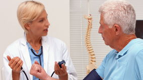Γιατρός που παίρνει τη πίεση του αίματος του ηλικιωμένου ασθενή απόθεμα βίντεο