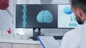 Γιατρός που παίρνει τις σημειώσεις και που μελετά από μια τρισδιάστατη ζωντανεψοντη ανίχνευση εγκεφάλου φιλμ μικρού μήκους