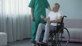 Γιατρός που παρακινεί τον άρρωστο ασθενή για να αναπτύξει τους μυς βραχιόνων μετά από τον κακό νωτιαίο τραυματισμό απόθεμα βίντεο