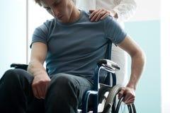 Γιατρός που παρηγορεί τη συνεδρίαση νεαρών άνδρων στην αναπηρική καρέκλα Στοκ Φωτογραφίες