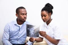 Γιατρός που παρουσιάζει ακτίνα X γονάτων στον ασθενή στοκ φωτογραφίες με δικαίωμα ελεύθερης χρήσης