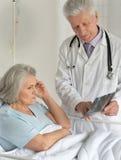 Γιατρός που παρουσιάζει ακτηνογραφία στο θηλυκό ασθενή Στοκ Εικόνες