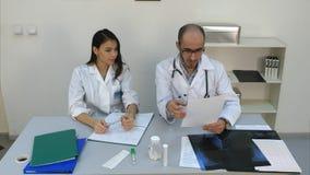 Γιατρός που παρουσιάζει γυναίκα βοηθός του πώς να διαβάσει το καρδιογράφημα ενώ αυτή που κάνει τις σημειώσεις στοκ φωτογραφίες