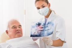 Γιατρός που παρουσιάζει οδοντική ακτίνα X στον αρσενικό ασθενή στοκ φωτογραφίες