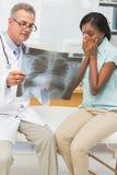 Γιατρός που παρουσιάζει στον ευτυχή ασθενή θετική θωρακική ακτίνα X της Στοκ Φωτογραφία