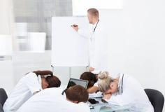 Γιατρός που παρουσιάζει στους συναδέλφους που κοιμούνται στο γραφείο Στοκ Εικόνα