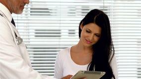 Γιατρός που παρουσιάζει ταμπλέτα στον έγκυο ασθενή φιλμ μικρού μήκους
