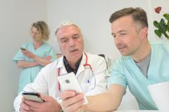 Γιατρός που παρουσιάζει τηλέφωνο της Mobil στο γιατρό Στοκ Εικόνα