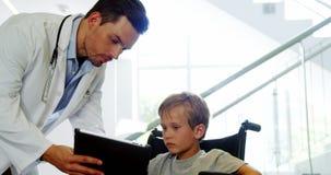 Γιατρός που παρουσιάζει ψηφιακή ταμπλέτα για να θέσει εκτός λειτουργίας το αγόρι απόθεμα βίντεο