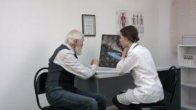 Γιατρός που παρουσιάζει mri στον παλαιό ασθενή και που εξηγεί κάτι απόθεμα βίντεο