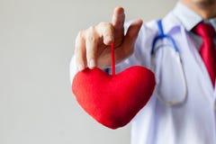 Γιατρός που παρουσιάζουν οίκτο και υποστήριξη που κρατά την κόκκινη καρδιά Στοκ φωτογραφία με δικαίωμα ελεύθερης χρήσης