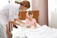 Γιατρός που ρυθμίζει την ενδοφλέβια σταλαγματιά για λίγο παιδί στοκ εικόνα με δικαίωμα ελεύθερης χρήσης