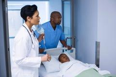 Γιατρός που ρυθμίζει IV σταλαγματιά ενώ ασθενής που βρίσκεται στο κρεβάτι στοκ εικόνα με δικαίωμα ελεύθερης χρήσης