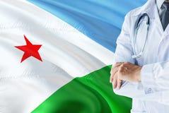 Γιατρός που στέκεται με το στηθοσκόπιο στο υπόβαθρο σημαιών του Τζιμπουτί Εθνική έννοια υγειονομικών συστημάτων, ιατρικό θέμα στοκ φωτογραφία με δικαίωμα ελεύθερης χρήσης