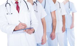 Γιατρός που στέκεται στη συνταγή γραψίματος ομάδας Στοκ Φωτογραφία
