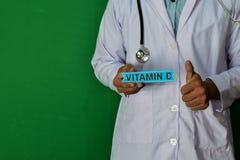 Γιατρός που στέκεται στο πράσινο υπόβαθρο Κρατήστε το κείμενο εγγράφου βιταμίνης C Ιατρική και έννοια υγειονομικής περίθαλψης στοκ εικόνες