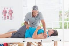 Γιατρός που τεντώνει μια πλάτη νεαρών άνδρων Στοκ Εικόνες