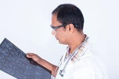 Γιατρός που φαίνεται των ακτίνων X περιοχή γονάτων ταινιών Στοκ φωτογραφία με δικαίωμα ελεύθερης χρήσης