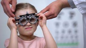 Γιατρός που φορά το οπτικό δοκιμαστικό πλαίσιο στο παιδί για να εντοπίσει τη μυωπία, θολωμένη όραση απόθεμα βίντεο