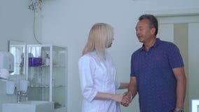 Γιατρός που χαιρετά το ενήλικο άτομο στο γραφείο της απόθεμα βίντεο