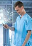 Γιατρός που χαμογελά στο κινητό τηλέφωνο με τα apps στο σύγχρονο δωμάτιο Στοκ Εικόνες
