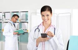 Γιατρός που χαμογελά στο τηλέφωνο, έννοια της ιατρικής κράτησης στοκ εικόνες με δικαίωμα ελεύθερης χρήσης