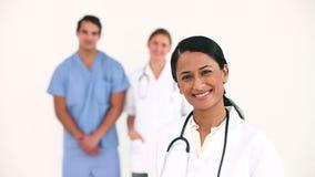 Γιατρός που χαμογελά ως στάση συναδέλφων της πίσω από την απόθεμα βίντεο