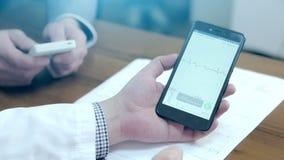 Γιατρός που χρησιμοποιεί ένα κινητό τηλέφωνο και μια ταμπλέτα Ένας αρσενικός γιατρός που χρησιμοποιεί τις ηλεκτρονικές συσκευές απόθεμα βίντεο