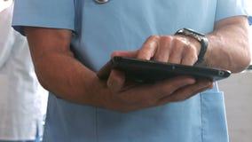 Γιατρός που χρησιμοποιεί την ταμπλέτα με τον ασθενή και το χειρούργο στο υπόβαθρο απόθεμα βίντεο