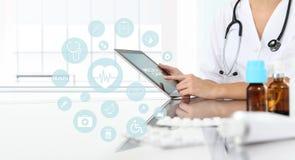 Γιατρός που χρησιμοποιεί την ταμπλέτα στο ιατρικό γραφείο με τα φάρμακα στο γραφείο Στοκ φωτογραφία με δικαίωμα ελεύθερης χρήσης
