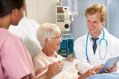 Γιατρός που χρησιμοποιεί την ψηφιακή ταμπλέτα κατόπιν διαβουλεύσεων με τον ανώτερο ασθενή Στοκ Φωτογραφίες