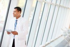 Γιατρός που χρησιμοποιεί την ψηφιακή ταμπλέτα στο διάδρομο του σύγχρονου νοσοκομείου Στοκ εικόνες με δικαίωμα ελεύθερης χρήσης