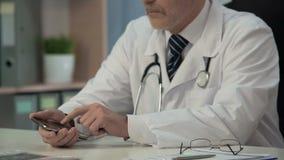 Γιατρός που χρησιμοποιεί τη νέα ιατρική εφαρμογή στη συσκευή, που ψάχνει τις απαραίτητες πληροφορίες φιλμ μικρού μήκους