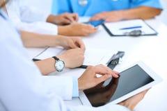 Γιατρός που χρησιμοποιεί τον υπολογιστή ταμπλετών στην ιατρική συνεδρίαση, κινηματογράφηση σε πρώτο πλάνο Ομάδα συναδέλφων στο υπ Στοκ Φωτογραφίες