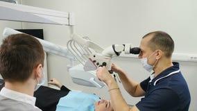 Γιατρός που χρησιμοποιεί το μικροσκόπιο Οδοντίατρος που θεραπεύει τον ασθενή στη σύγχρονη οδοντική κλινική Εργασίες Orthodontist  φιλμ μικρού μήκους