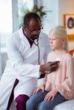 Γιατρός που χρησιμοποιεί το στηθοσκόπιο ακούοντας τους πνεύμονες του κοριτσιού στοκ εικόνα