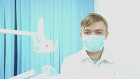 Γιατρός στη μάσκα και λευκό παλτό στο υπόβαθρο του δωματίου επεξεργασίας μέσα Ο ελκυστικός καλυμμένος γιατρός είναι έτοιμος να αρ φιλμ μικρού μήκους