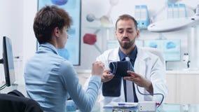 Γιατρός στη σύγχρονη δυνατότητα ιατρικής έρευνας που μετρά τη πίεση του αίματος σε μια νέα γυναίκα απόθεμα βίντεο