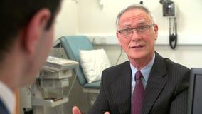 Γιατρός στη χειρουργική επέμβαση που μιλά με τον ανώτερο αρσενικό ασθενή απόθεμα βίντεο